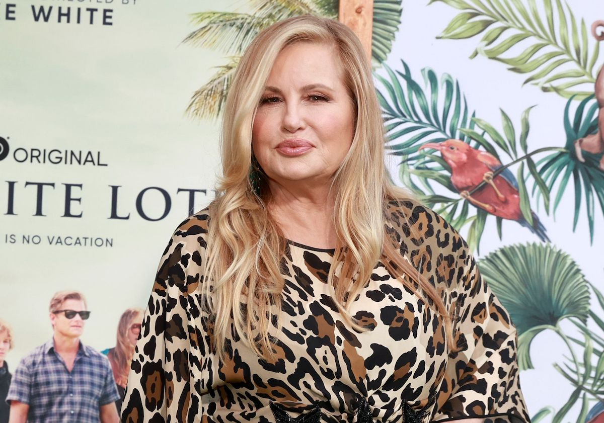 Jennifer Coolidge attends the Los Angeles premiere of HBO's 'The White Lotus.' She wears a long-sleeved leopard print dress, her long blonde hair is styled down, and she stands in front of a tropical backdrop that says 'The White Lotus' and shows a photo of the cast.