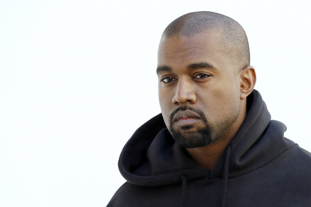 Kanye West looks ahead in front of a white backdrop