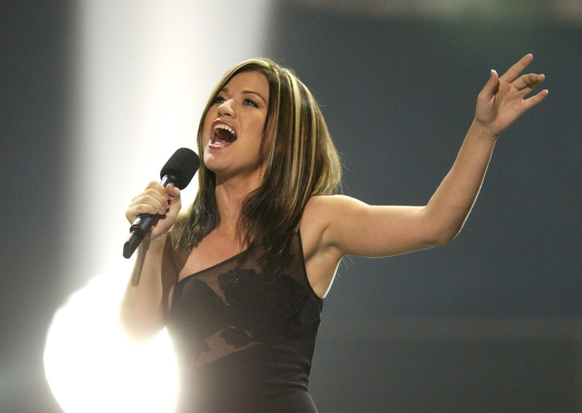 Kelly Clarkson raising her arm and singing into a microphone