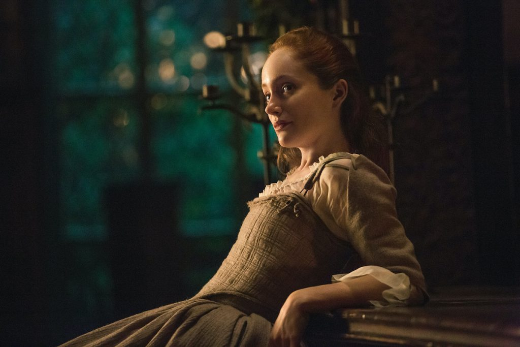 Lotte Verbeek as Geillis Duncan in 'Outlander' Season 1. Verbeek leans her arms and back against a wooden counter at nighttime. She wears a beige dress fitting the 1700s Scotland time period. There are large brass candlesticks behind her and large windows showing trees outside.  Given Geillis' time traveling abilities, 'Outlander' fans wondered if Claire and Geillis are related. As it turns out, they are. And they're connected by another time traveler.
