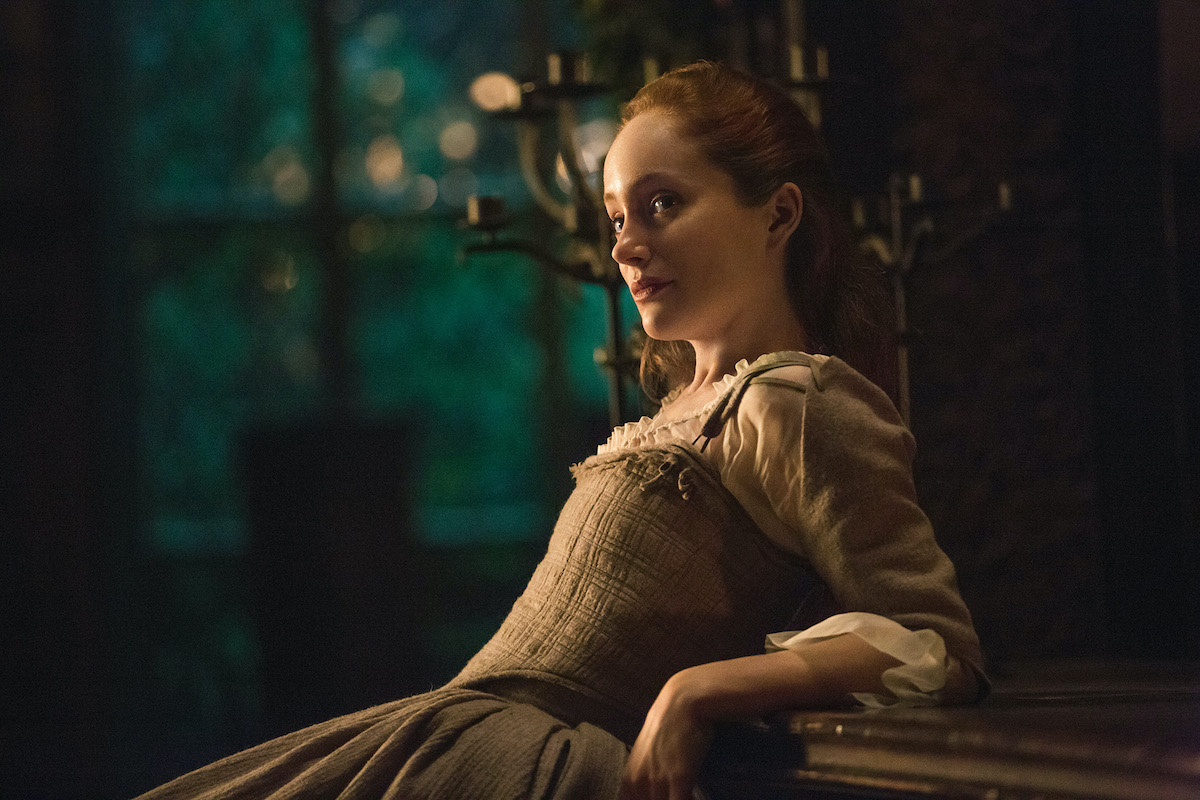 Lotte Verbeek as Geillis Duncan in 'Outlander' Season 1. Verbeek leans her arms and back against a wooden counter at nighttime. She wears a beige dress fitting the 1700s Scotland time period. There are large brass candlesticks behind her and large windows showing trees outside. 'Outlander's Geillis Duncan was featured in season 1, season 2, and season 3, and Verbeek says she could come back to the 'Outlander' cast in the future. Fans are hoping she will be part of the 'Outlander' Season 6 cast.