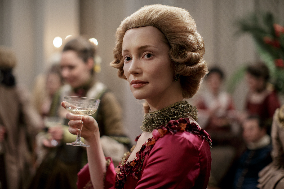 Lotte Verbeek as Geillis Duncan in 'Outlander' Season 3. She wears a magenta gown with a strawberry blonde, women's style colonial wig and holds a glass of champagne in her hand. Geillis Duncan was in 'Outlander' Season 1, 2, and 3, and given her time traveling abilities, she could be part of 'Outlander' Season 6.