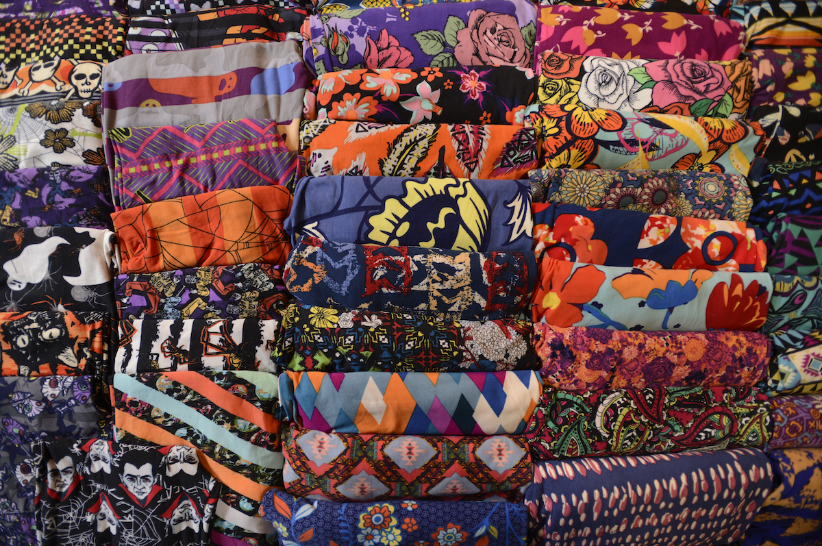 Stacks of colorfully printed LuLaRooe leggings folded neatly in rows.
