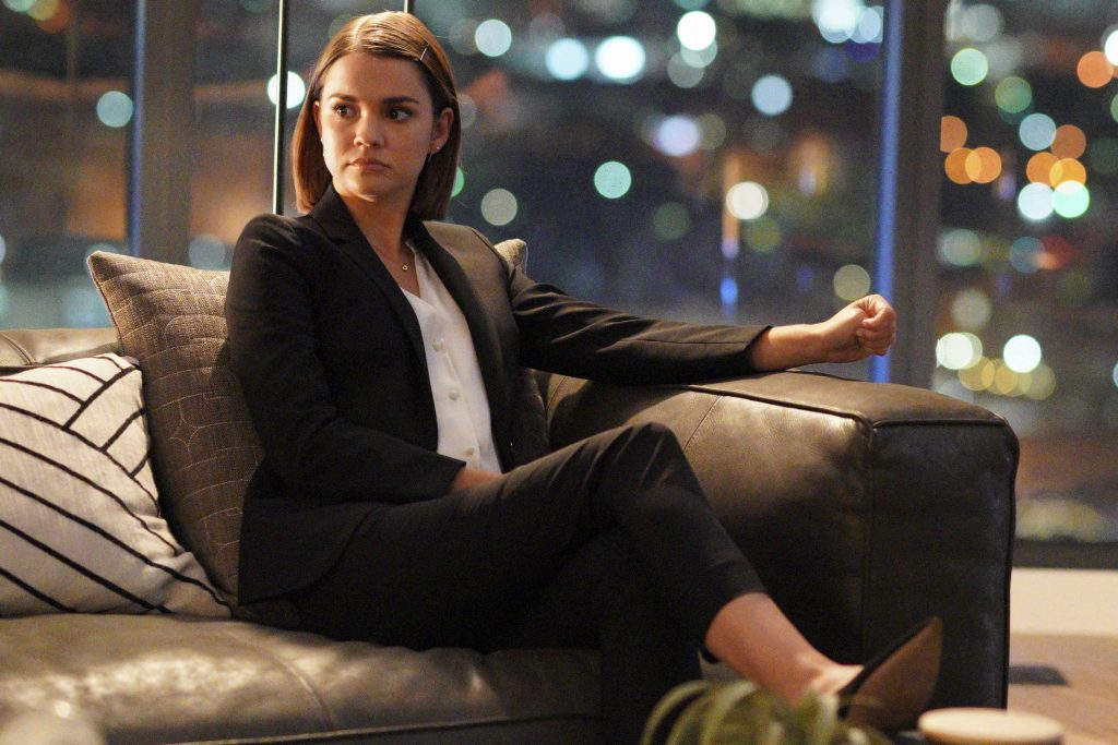 Maia Mitchell sits on a couch while wearing her lawyer suit on the set of 'Good Trouble.'