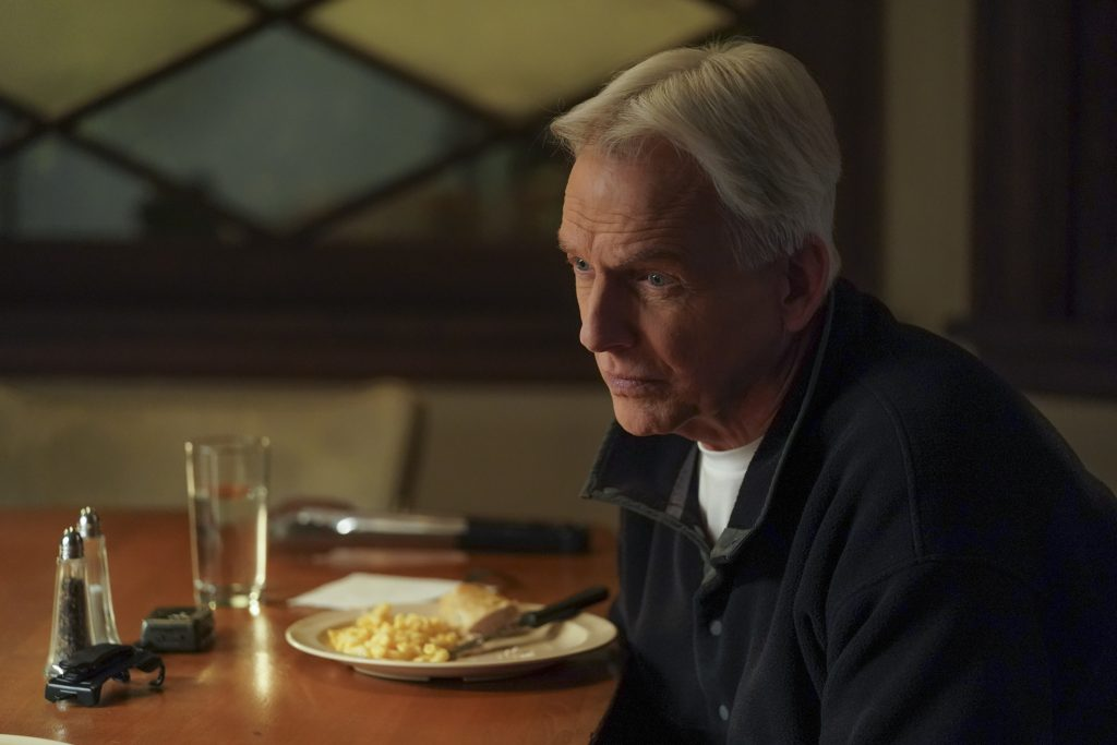 Mark Harmon sitting in front of a plate of food on 'NCIS.'