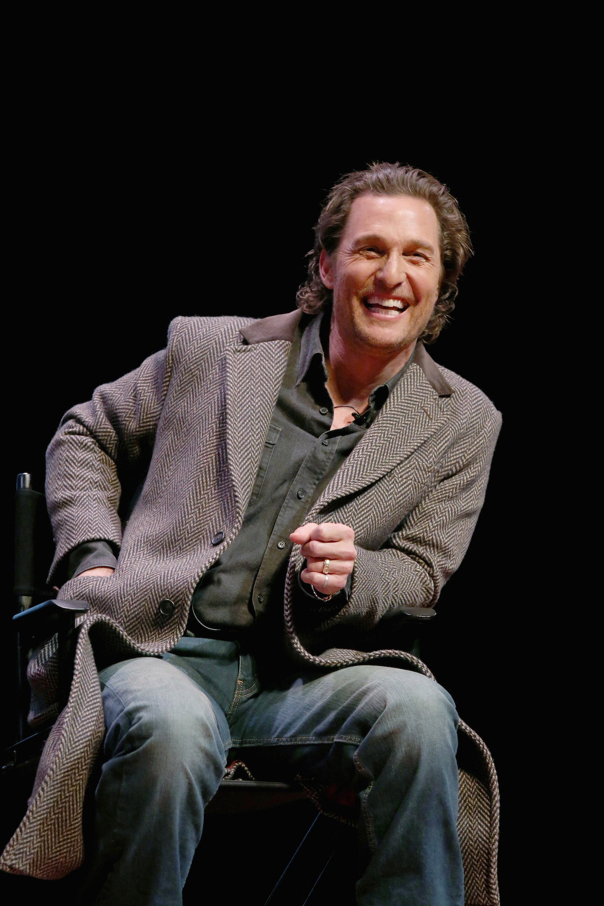 Matthew McConaughey sits on stage in a brown patterned coat , as he smiles to an audience on stage