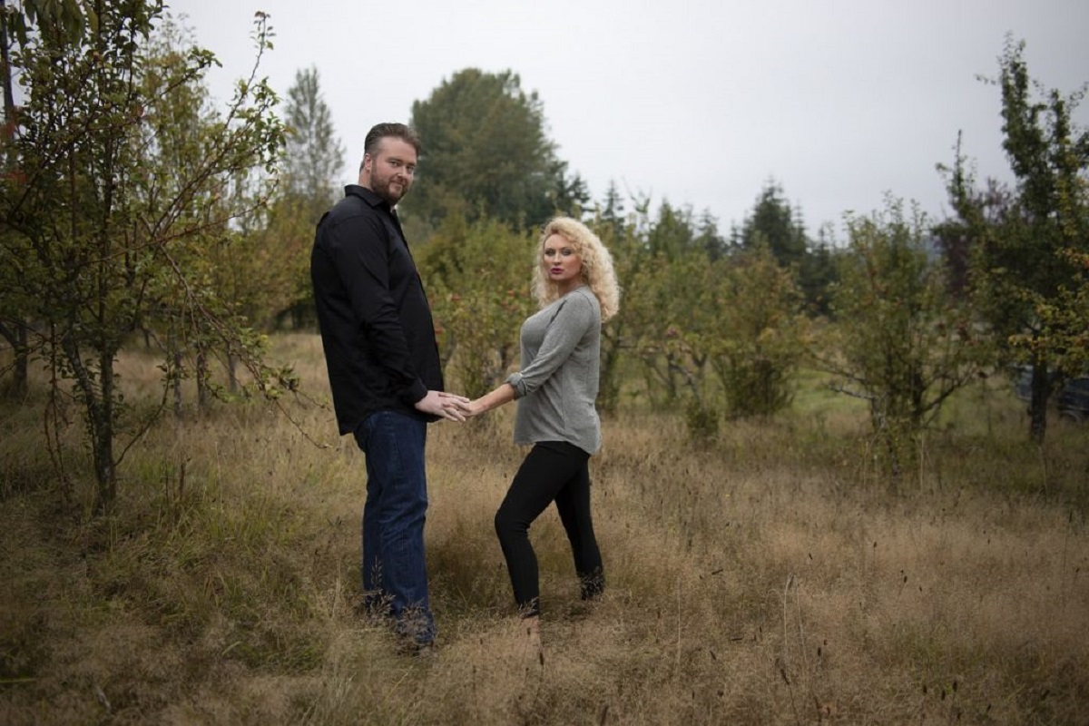 Mike and Natalie on '90 Day Fiancé', holding hands in a field, facing each other but looking at the camera.