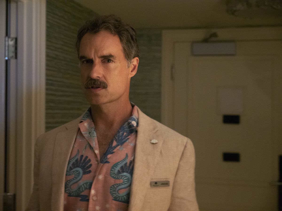 Murray Bartlett as Armond in 'The White Lotus' on HBO. The photo is from 'The White Lotus' poop scene in the season 1 finale, during which Armond sneaks into Shane Patton's room and poops in a suitcase. He stands in the entryway of a hotel suite wearing a pink button-down shirt with blue tropical print and a light beige suit jacket.