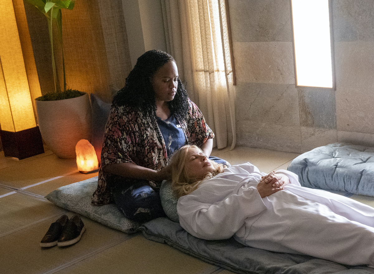 Natasha Rothwell and Jennifer Coolidge in HBO's 'The White Lotus.' Coolidge lays on her back on the floor while wearing a white robe and closing her eyes and holding her hands on her stomach as Rothwell massages her head. A Himalayan salt lamp is on the floor behind them. Rothwell sits on a blue, coral patterned pillow and Coolidge lays on a long, blue cushion.