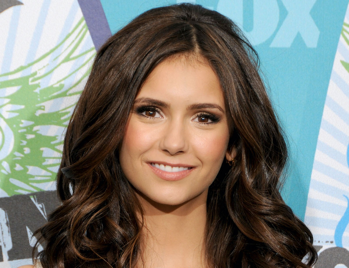 Nina Dobrev of 'The Vampire Diaries' poses and smiles in the press room for Teen Choice 2010. Her hair is down and curled, and she wears a cream colored strapless dress. Nina Dobrev played Elena Gilbert, Katherine Pierce, and Amara — the Petrova doppelgängers — in 'The Vampire Diaries' Season 5.