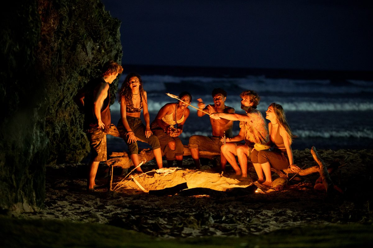 'Outer Banks' stars Rudy Pankow, Madison Bailey, Carlacia Grant, Jonathan Daviss, Chase Stokes, and Madelyn Cline sitting around a fire in season 2