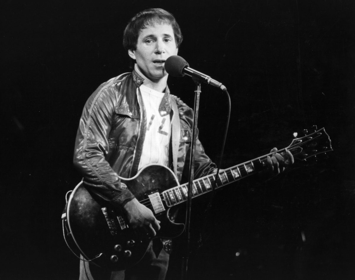 Paul Simon with a microphone and a guitar