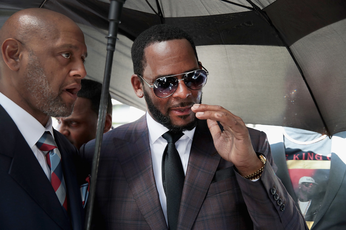 R. Kelly (R) leaves the Leighton Criminal Courts Building following a hearing on June 26, 2019 in Chicago, Illinois. Prosecutors turned over to Kelly's defense team a DVD that alleges to show Kelly having sex with an underage girl in the 1990s. Kelly has been charged with multiple sex crimes involving four women, three of whom were underage at the time of the alleged encounters.