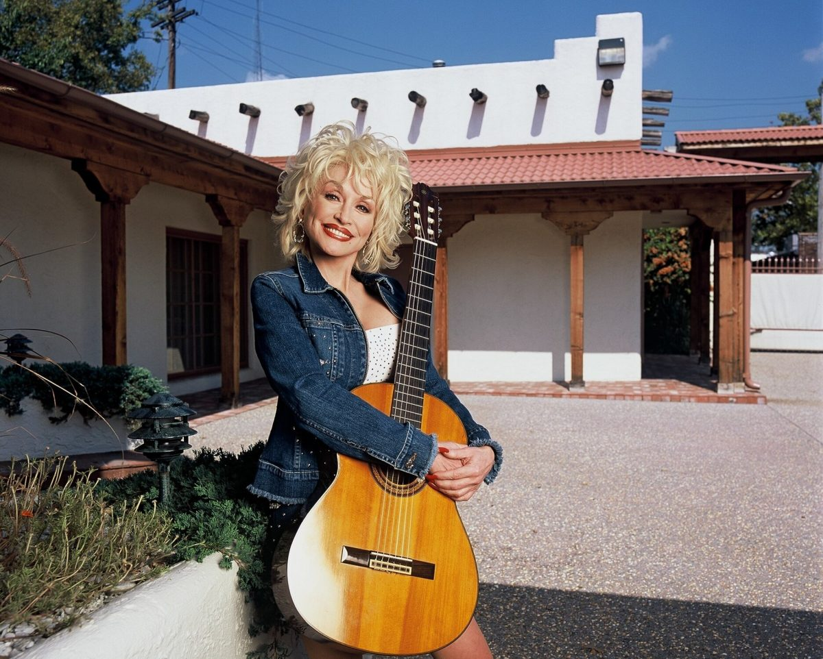 Dolly Parton poses with her guitar outside her offices in Nashville, Tennessee in 2001.