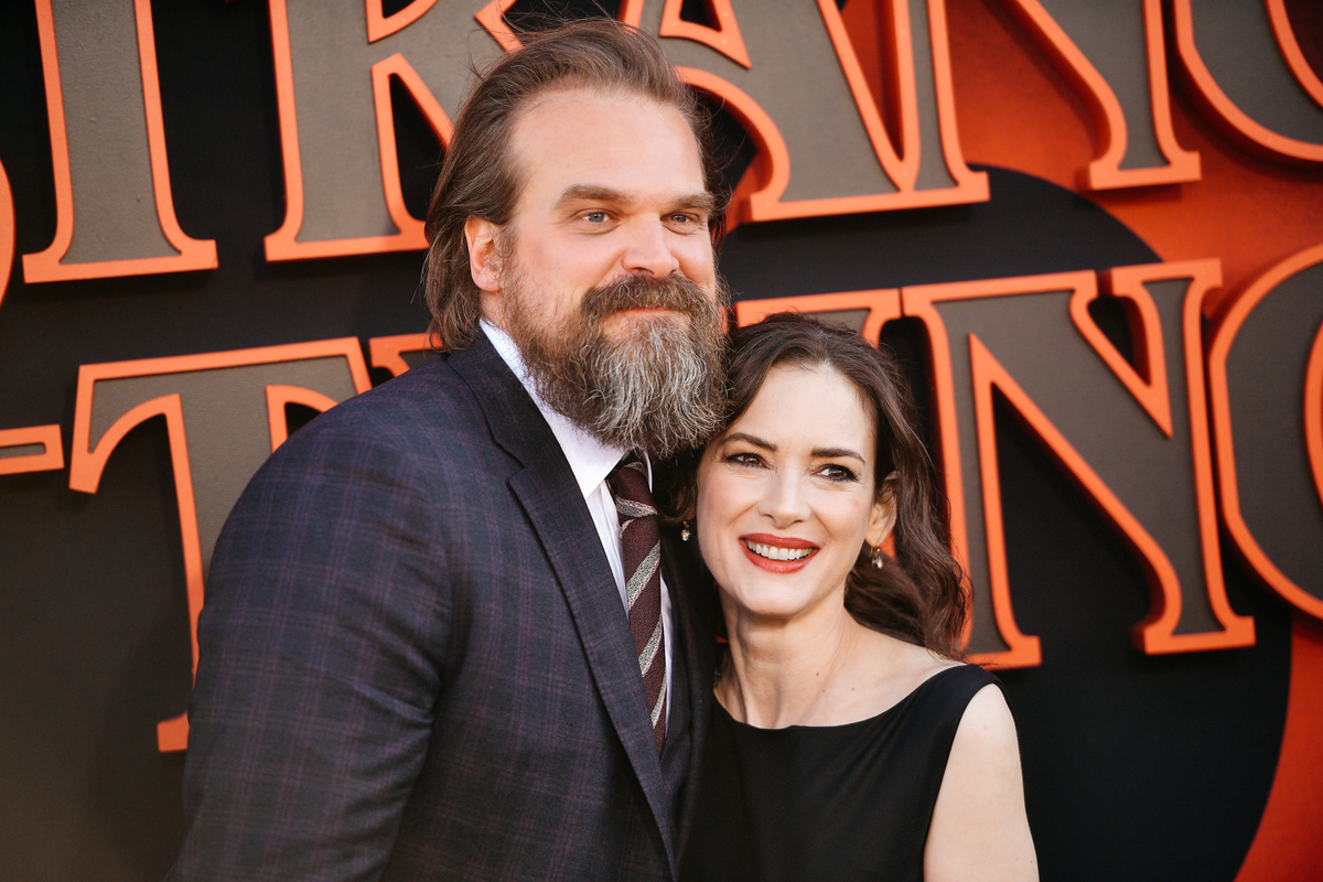 David Harbour in a black suit hugging Winona Ryder in a black dress at the 'Stranger Things' 3 premiere.