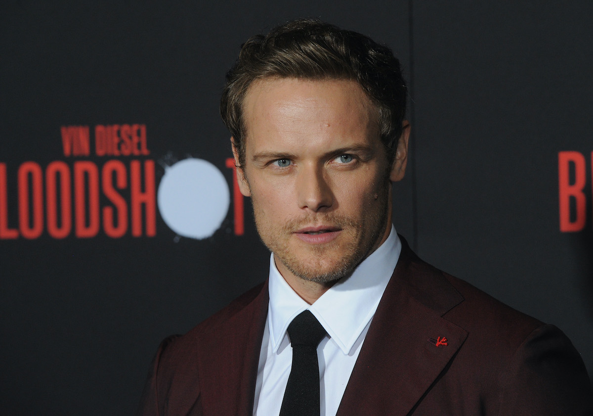 Sam Heughan at the 'Bloodshot' premiere on March 10, 2020. He wears a crimson suit with a white shirt and black necktie as he stands in front of a black backdrop that says 'Vin Diesel BLOODSHOT' in red lettering.