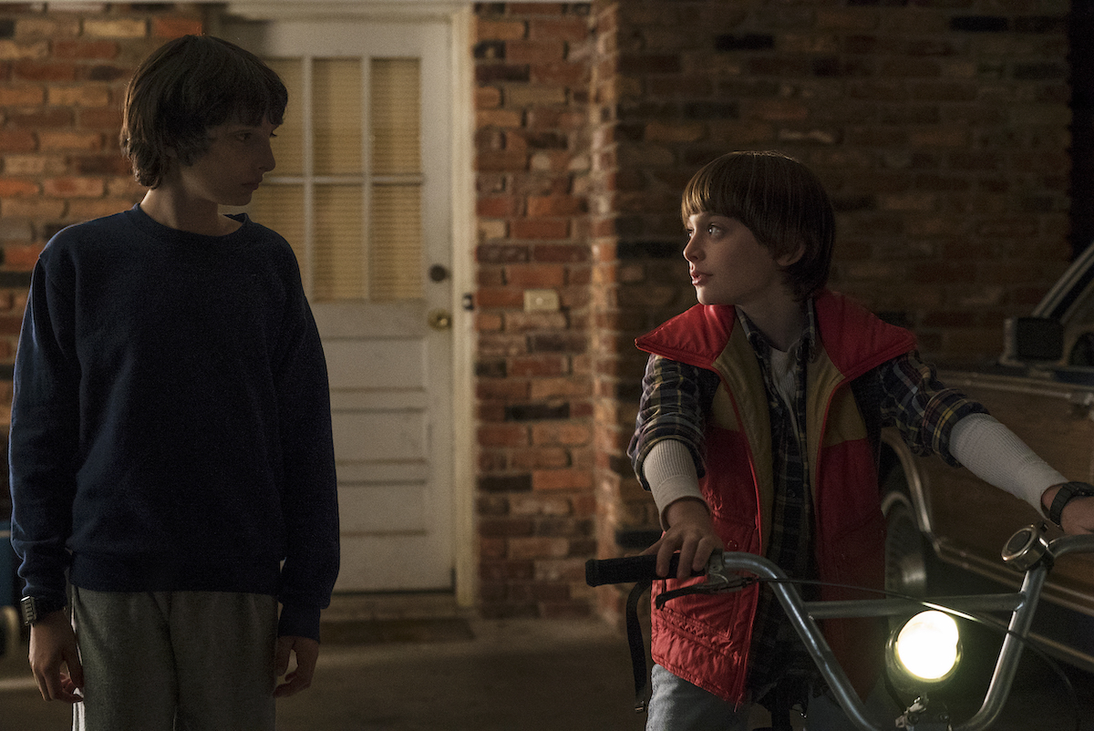 'Stranger Things' characters Mike Wheeler (Finn Wolfhard), in a blue sweatshirt and gray sweatpants and talks to Will Byers (Noah Schnapp) in a red puffy vest sitting on a bikee.