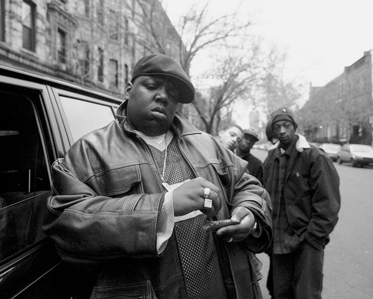 The Notorious B.I.G. in front of a car