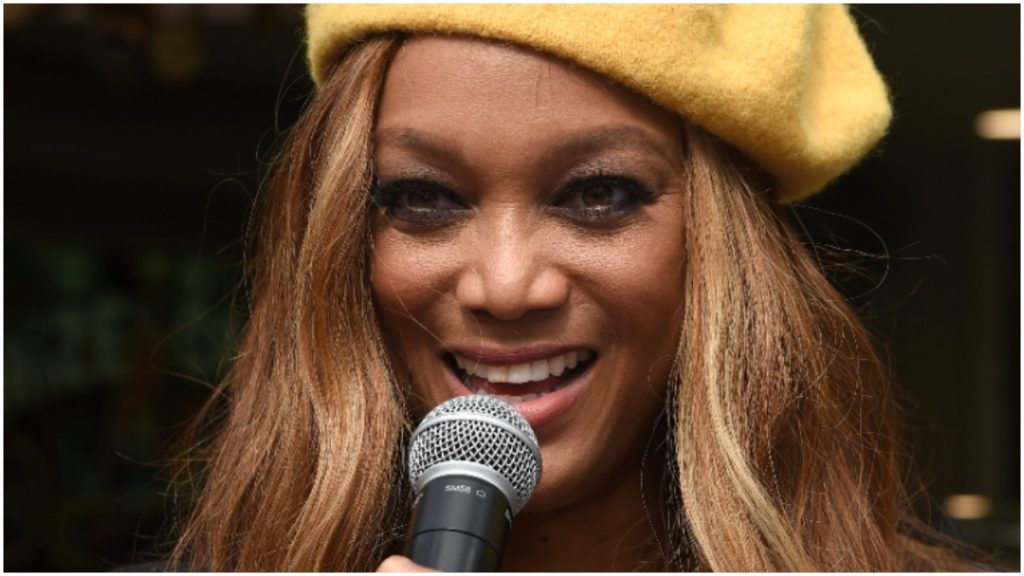 tyra banks wears a yellow hat while holding a microphone