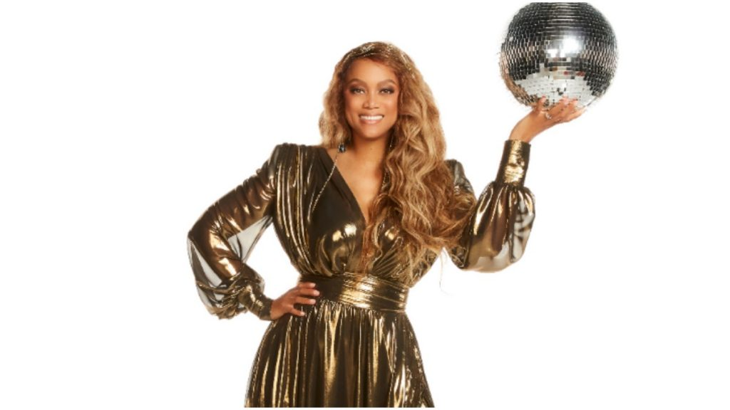 Tyra Banks holds a disco ball in DWTS promo.