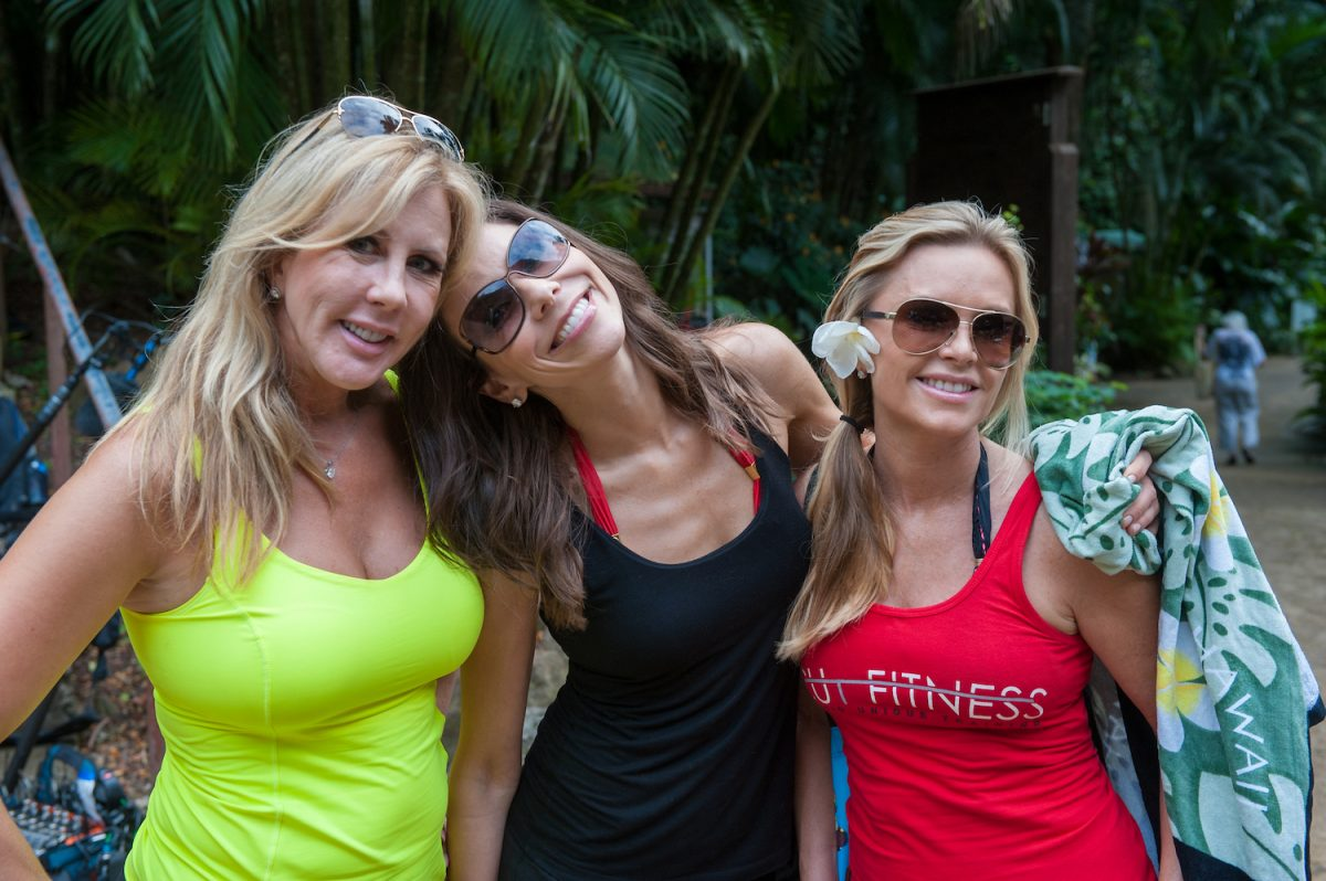 Vicki Gunvalson wearing a neon green top and shades, Heather Dubrow leaning her head on Vicki, and Tamra Judge smiling with shades on and a flower on her ear