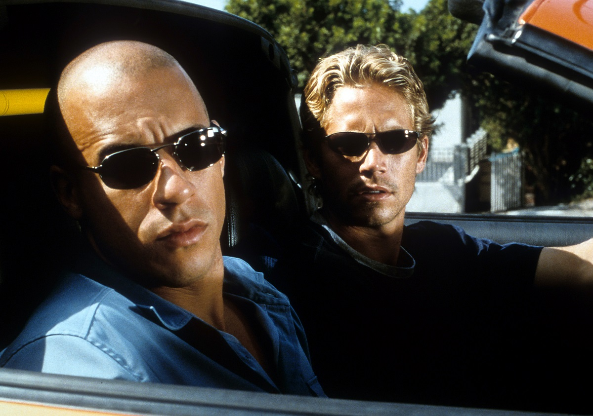 Vin Diesel and Paul Walker looking from car in a scene from the film 'The Fast And The Furious.' 2001.