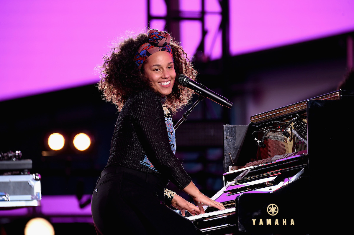 Alicia Keys wears an all black top and black bottoms as she smiles and plays the piano on stage at Times Square on October 9, 2016 in New York City.