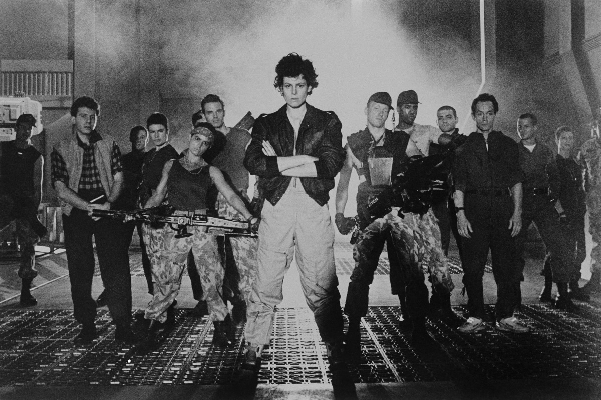 Sigourney Weaver and the cast of 'Aliens' looking at the camera.