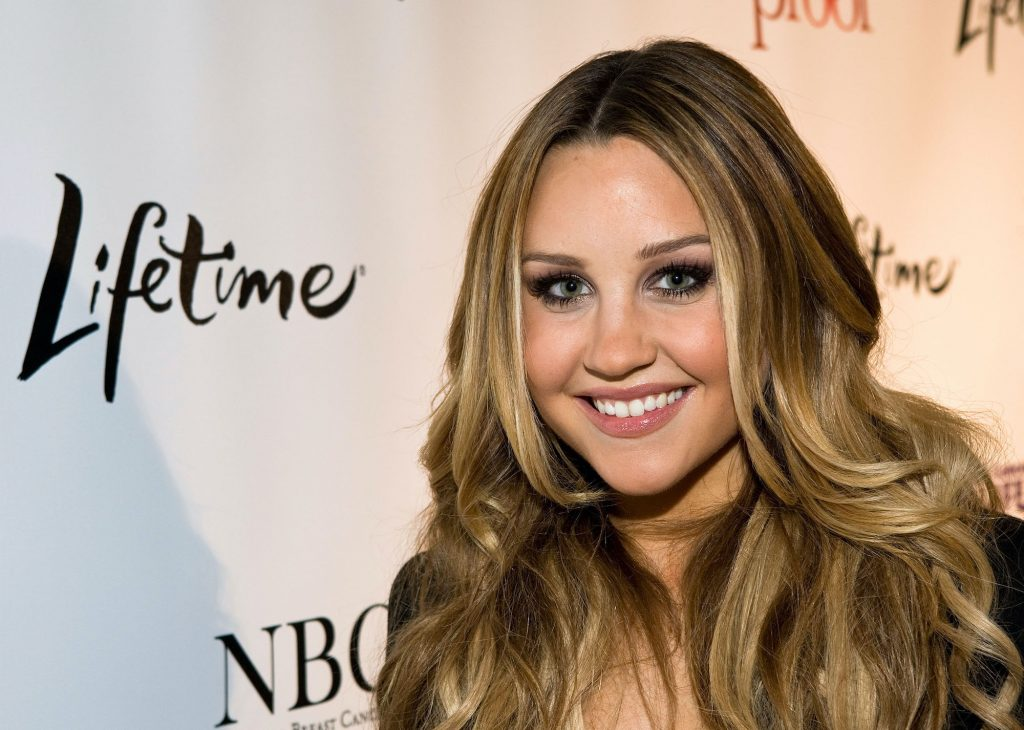 Amanda Bynes smiling in front of a white background
