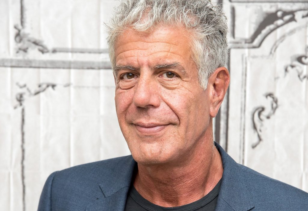 Anthony Bourdain smiling in front of a white background