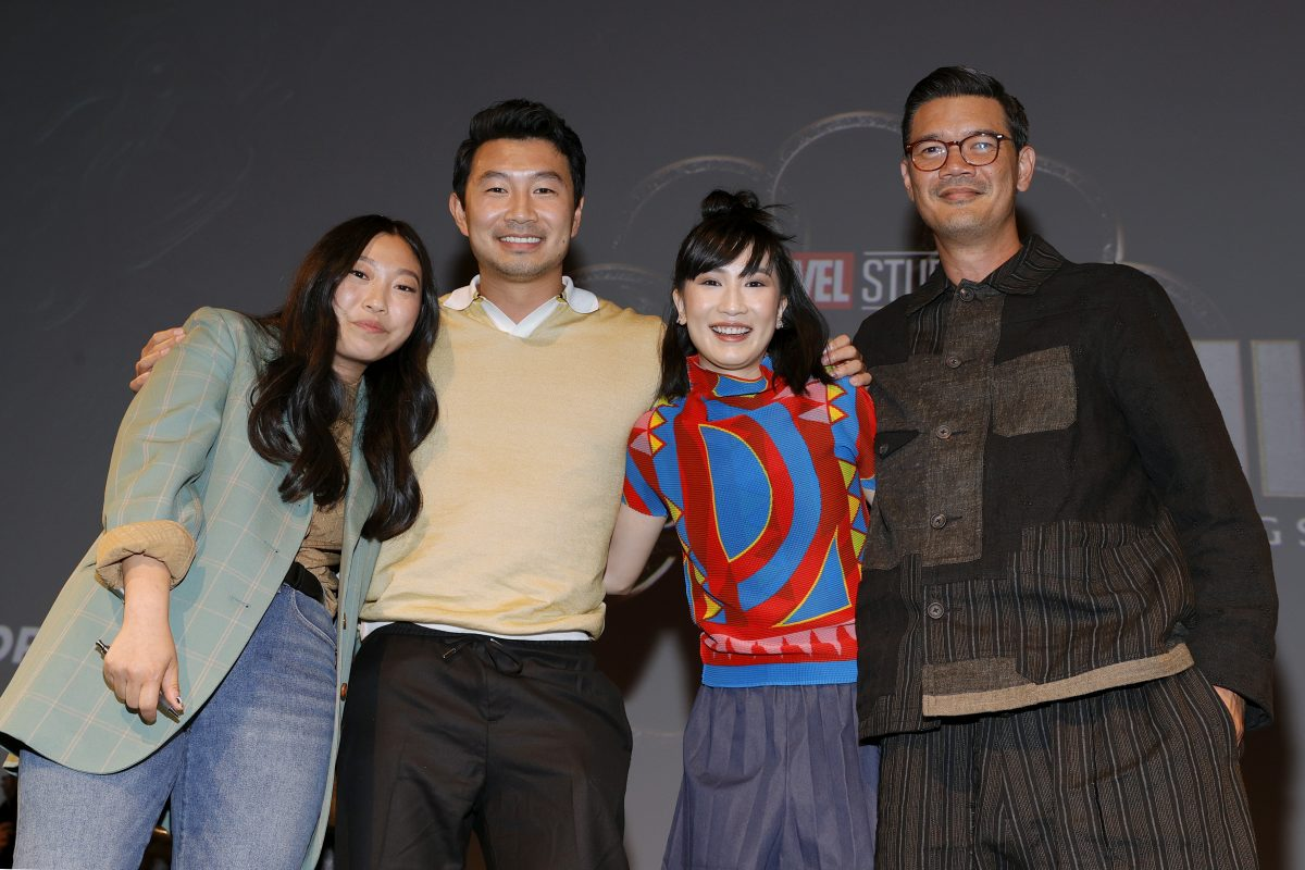 Awkwafina, Simu Liu, Meng'er Zhang and Destin Daniel Cretton standing together in front of a black background.