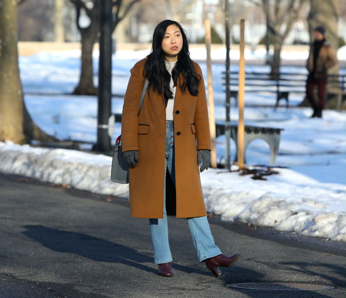Awkwafina wears a brown coat and jeans as she looks on while filming a scene from 'Awkwafina Is Nora From Queens' in 2021