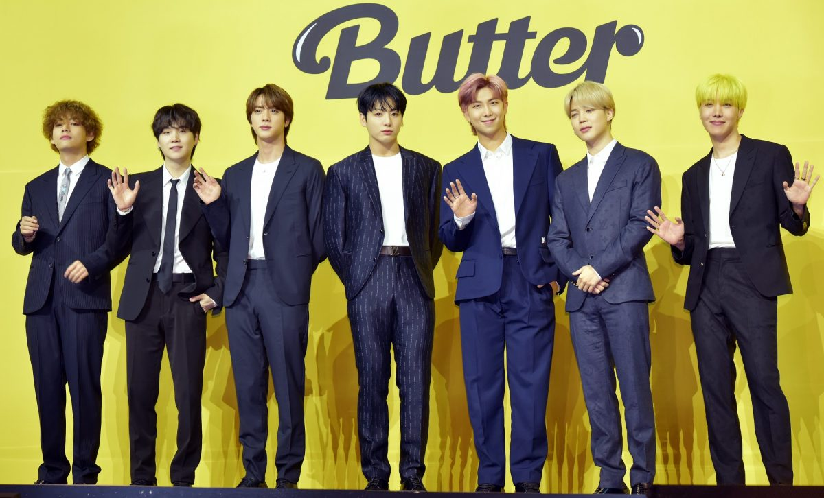 V, Suga, Jin, Jungkook, RM, Jimin, and J-Hope stand in front of a yellow backdrop with the word 'Butter'