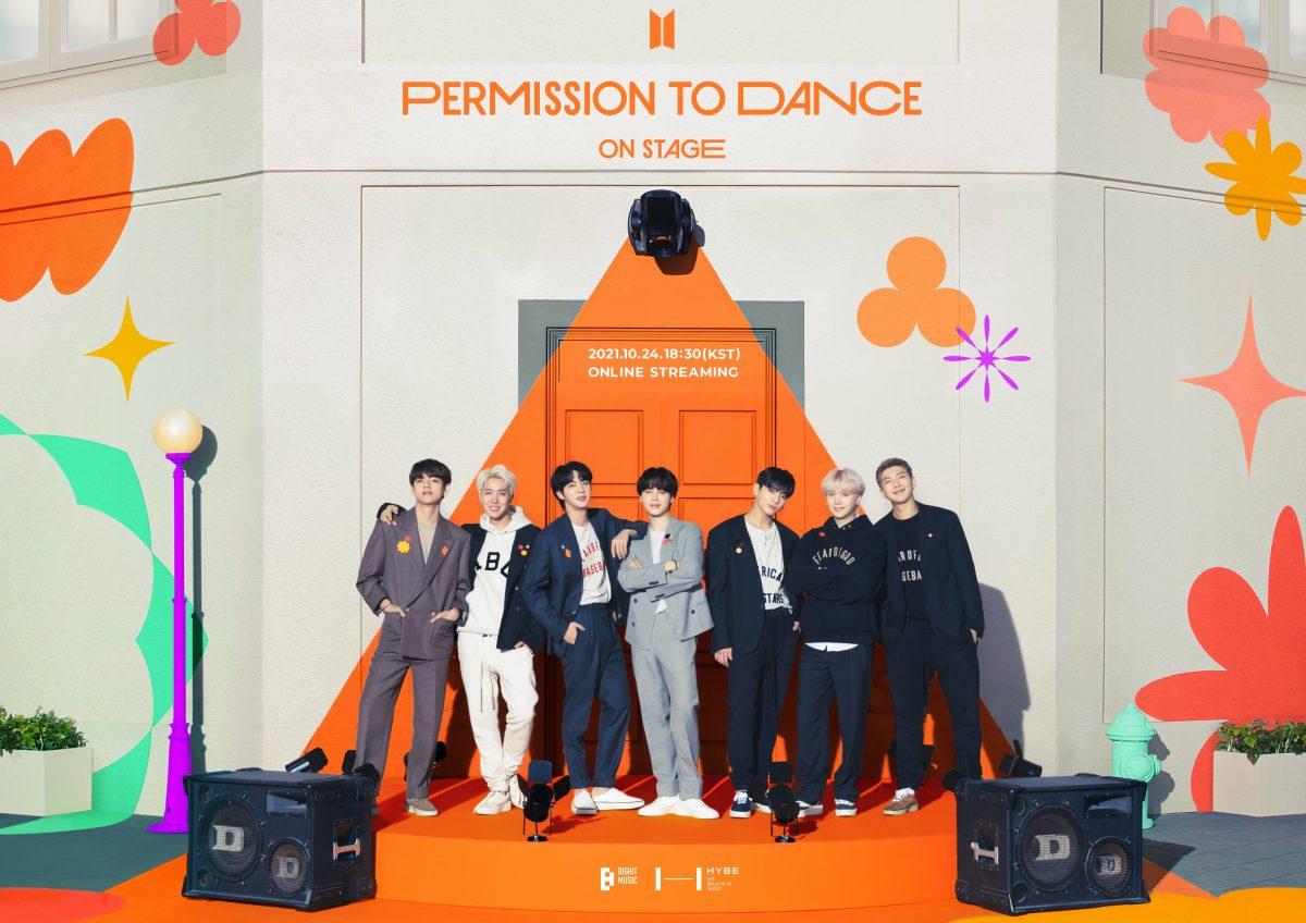 BTS's V, J-Hope, Jin, Jimin, Jungkook, Suga, and RM stand on orange stage in front of speakers