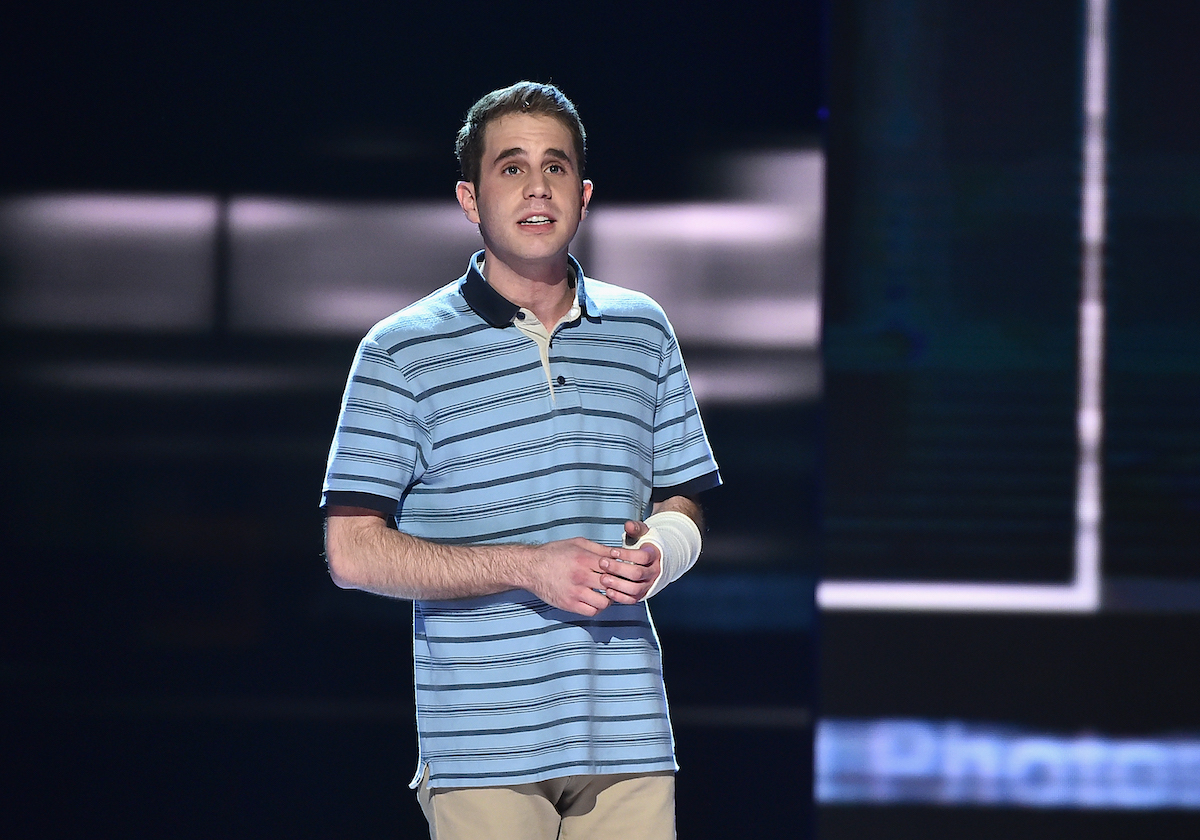 Ben Platt performing a song from 'Dear Evan Hansen' at the 2017 Tony Awards. He stands on a large stage wearing a blue, striped polo shirt and khaki pants with a white cast on his left arm. Platt originated the role of Evan Hansen in the Broadway show and reprises the role in the upcoming 'Dear Evan Hansen' movie. And Platt says the movie's ending changes the Broadway show's ending, which did draw some criticism from theatergoers.