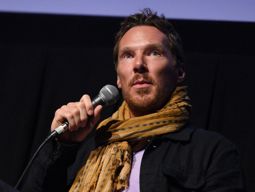 Benedict Cumberbatch holds a microphone. He's wearing a mustard yellow scarf.