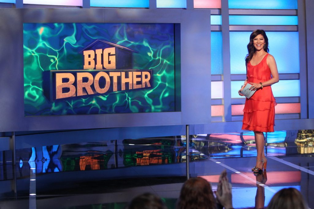 Julie Chen Moonves on 'Big Brother' stands on stage wearing a red dress.