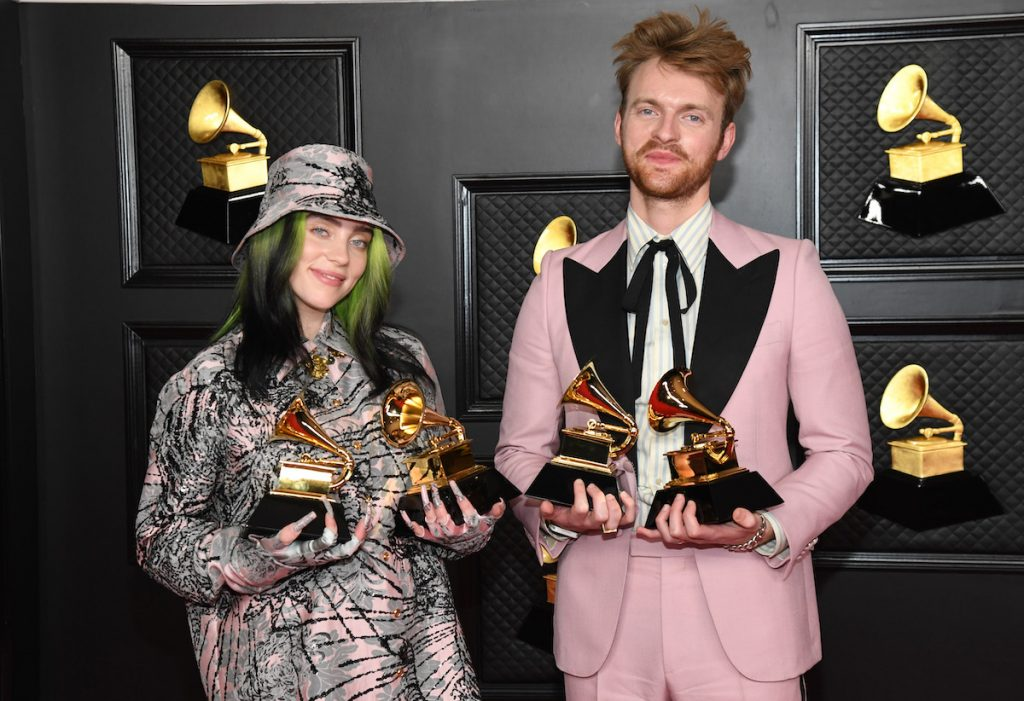 Billie Eilish and Finneas O'Connell holding four Grammy awards.