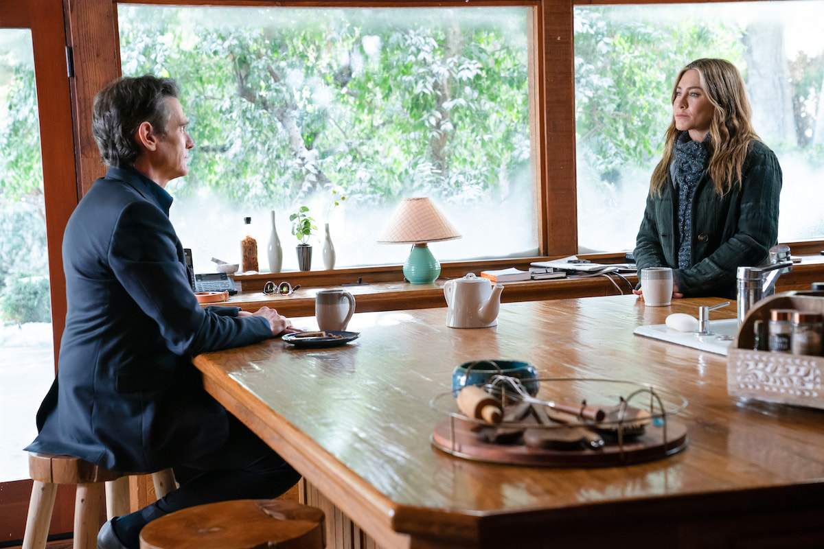Billy Crudup and Jennifer Aniston sit across from each other at a kitchen island in 'The Morning Show' Season 2 Episode 1: 'My Least Favorite Year'