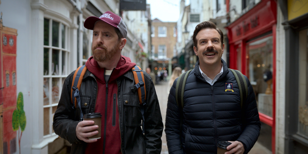 Brendan Hunt and Jason Sudeikis hold coffee cups as they walk down a street in 'Ted Lasso' Season 2