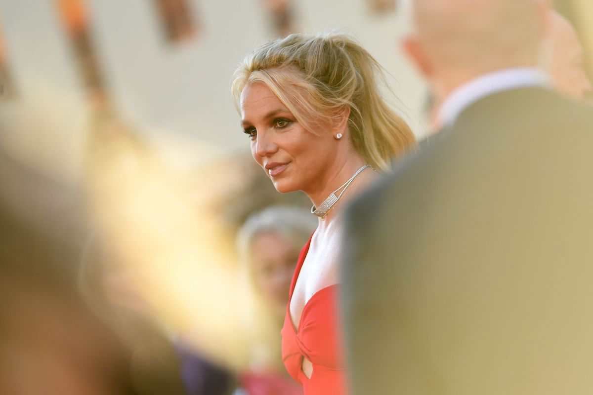 """Britney Spears is in a red gown as she arrives for the premiere of Sony Pictures' """"Once Upon a Time... in Hollywood"""" in 2019."""