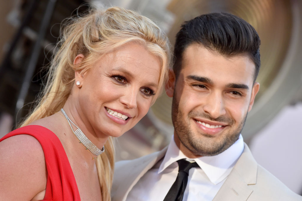 Britney Spears and Sam Asghari walk the red carpet. Spears is in a red dress while Asghari wears a tan suit.