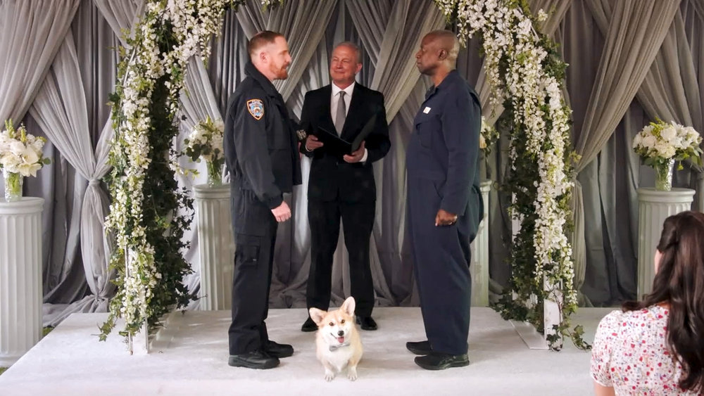Kevin and Captain Holt stand with their dog Cheddar while renewing their wedding vows in 'Brooklyn Nine-Nine'
