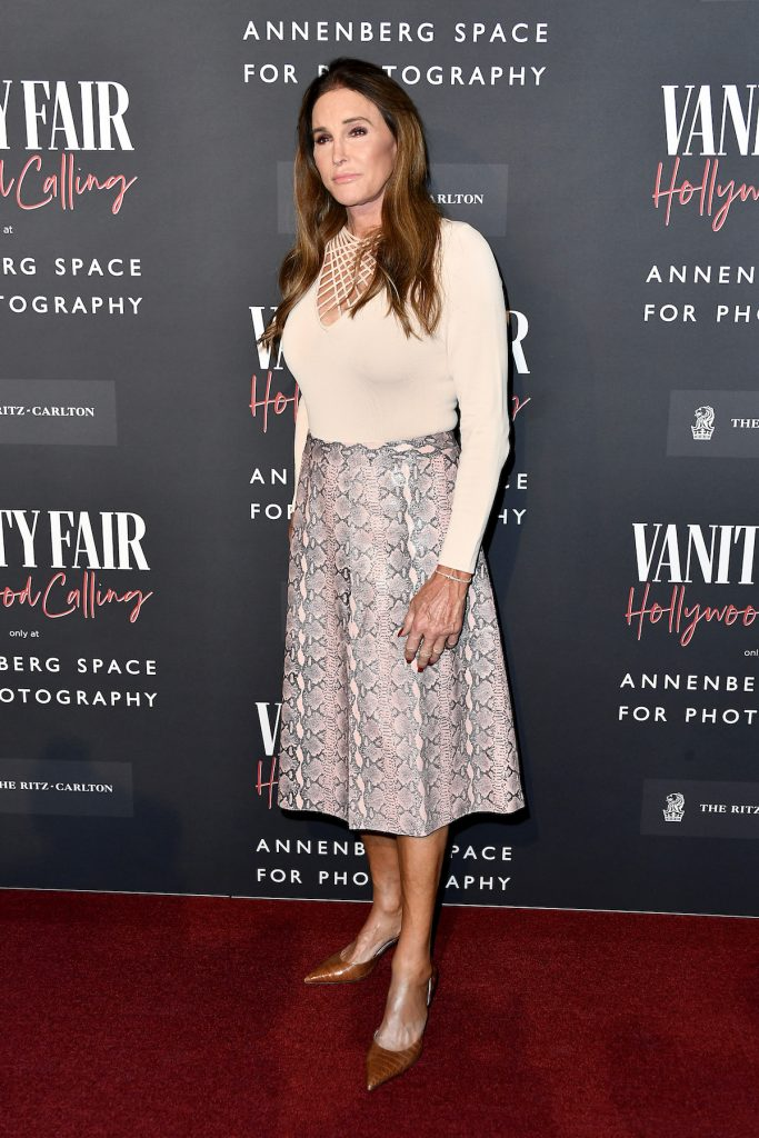 Caitlyn Jenner poses in a snakeskin skirt and white top at an event.