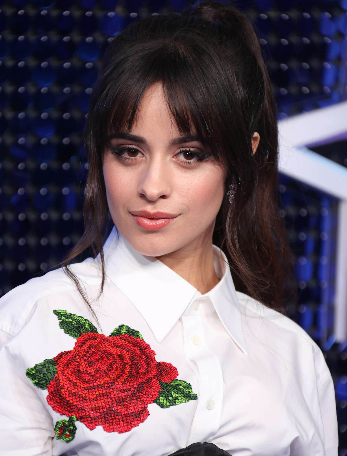 Camila Cabello wears a white top with a large red rose on it at an event.