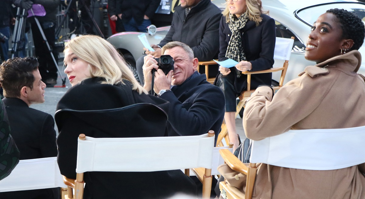 Lea Seydoux on the left and Lashana Lynch on the right both sitting on chairs looking up at something that Daniel Craig is taking a picture of.