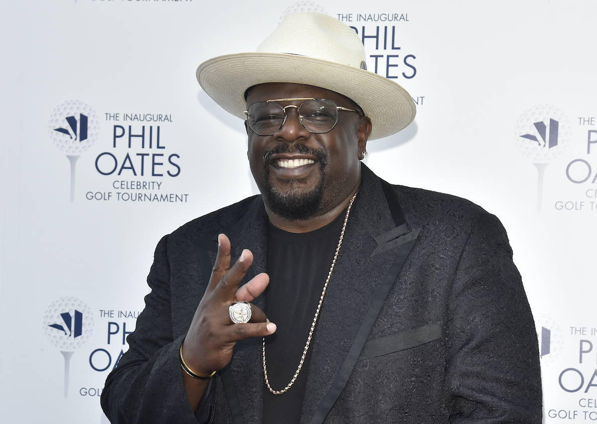 2021 Emmy Awards host, Cedric the Entertainer, smiles wearing a black suit and a white hat
