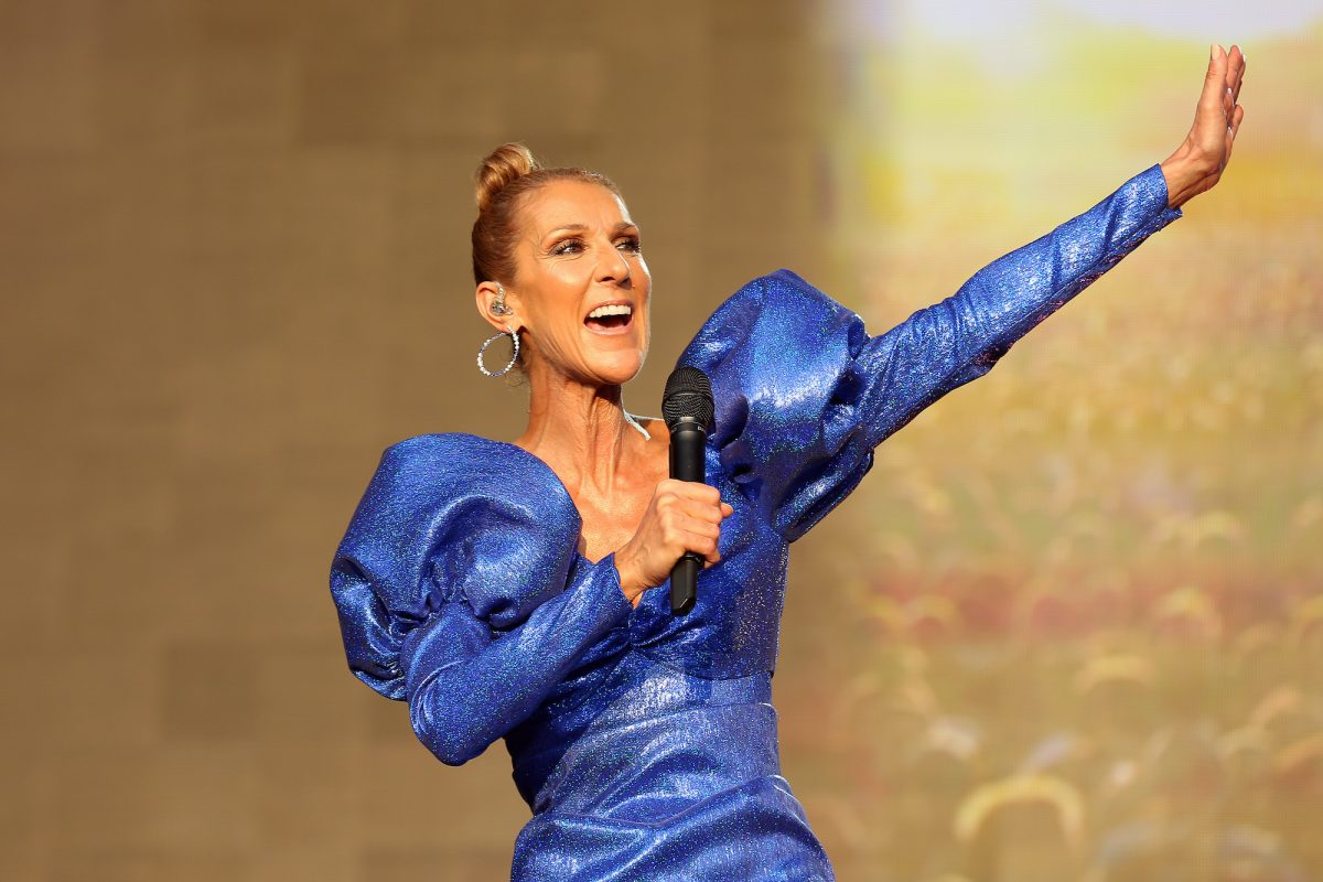 Celine Dion performs live on stage at the British Summer Time Hyde Park at Hyde Park concert on July 05, 2019 in London, England. She wears a bright blue shimmering jumpsuit with puffy sleeves and her hair pulled back in a bun. She sings into a microphone as she outstretches her left arm.