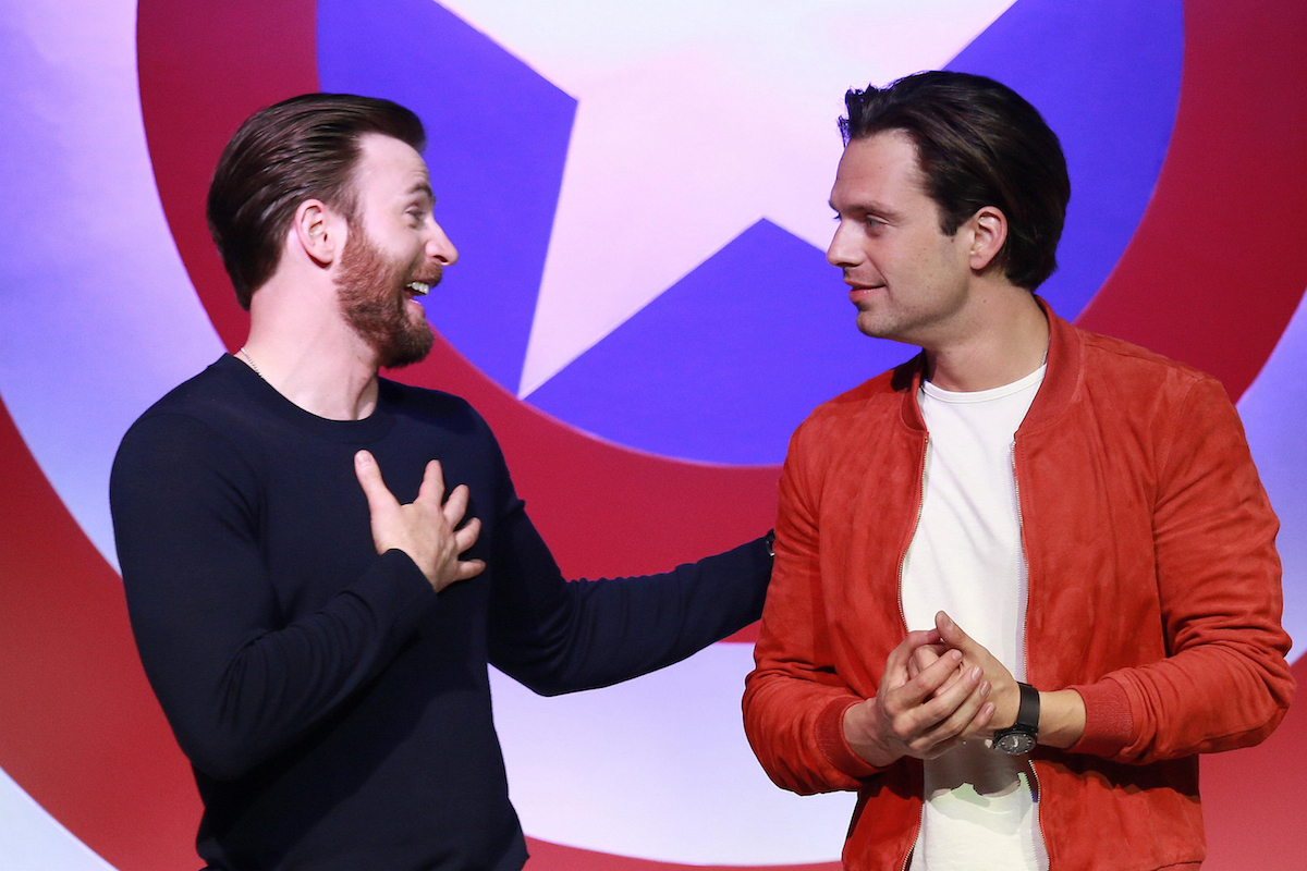 Chris Evans and Sebastian Stan smiling at each other