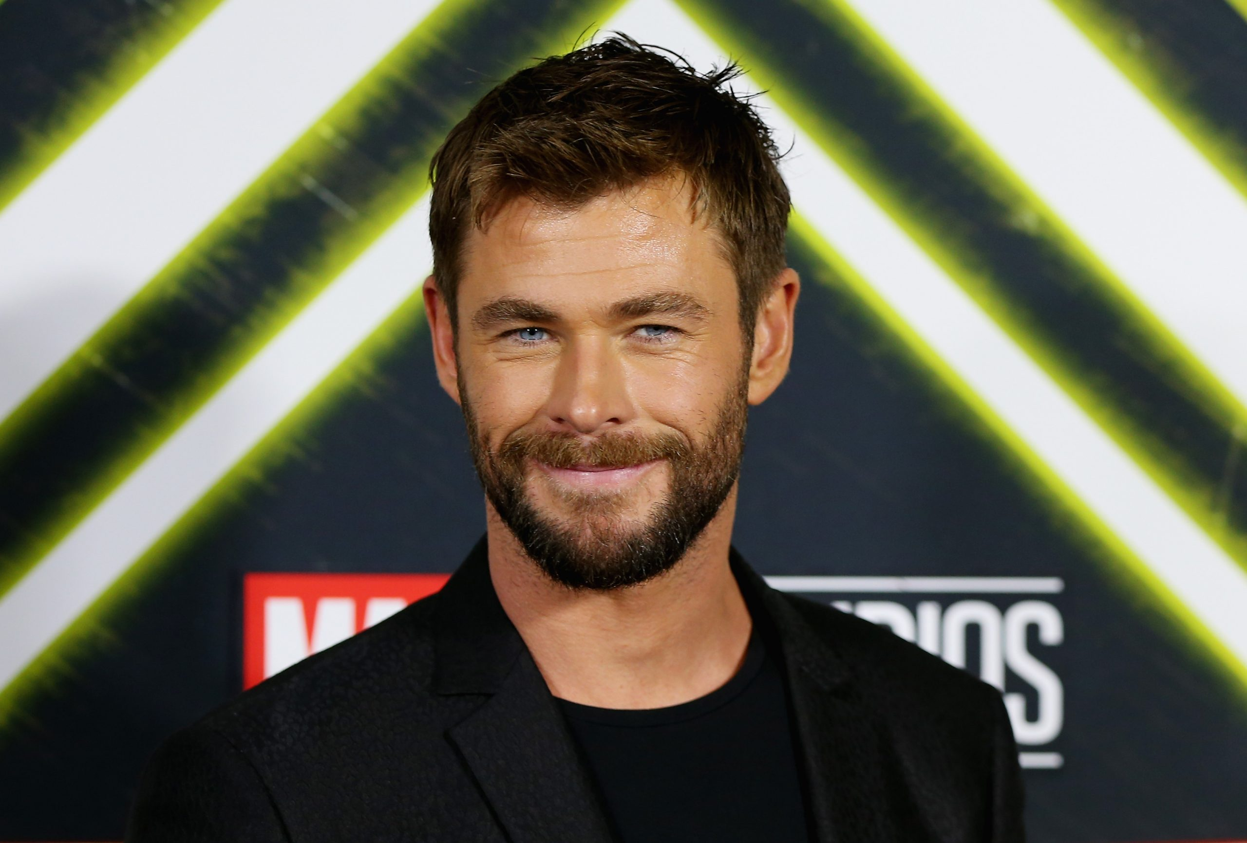 Chris Hemsworth, star of 'What If...?' Season 1 Episode 7 wears a black suit over a black shirt.
